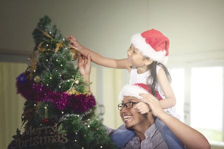 Happy father helping his daughter to decorating a Christmas tree in the living room at home Stok Fotoğraf
