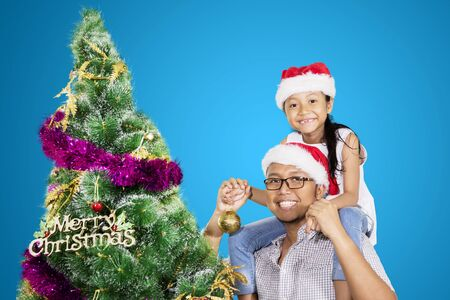 Happy father and his daughter looking at the camera while standing near a Christmas tree in the studio