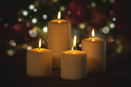 Close up of white Christmas candles with blurred twinkling light background