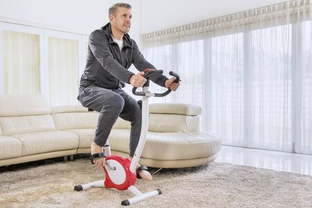 Caucasian man wearing sportswear while training with a spin bike in the living room. Shot at home