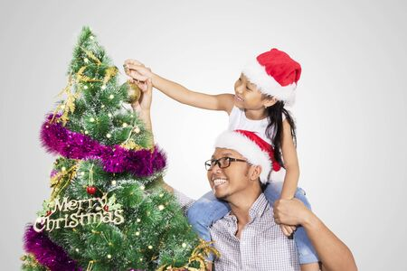 Young father helping his daughter to putting an ornament in a Christmas tree, isolated on white