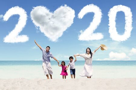 Portrait of cheerful family running on the beach with clouds shaped heart and numbers 2020 in the sky
