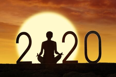 Rear view of silhouette woman practice yoga with number 2020 at sunrise time Stock Photo