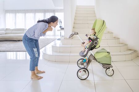 Happy woman playing with her baby in a stroller while standing in the living room at home Stockfoto