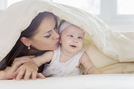Close up of young mother kissing her baby girl while lying under a blanket in the bedroom. Shot at home