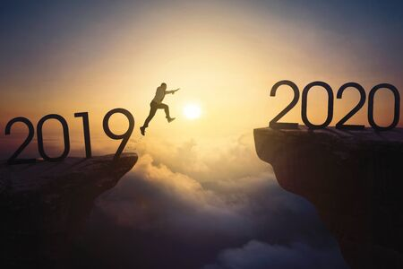 New year concept. Asian businessman jumping gap on the cliff from number 2019 to number 2020. Shot at sunrise time