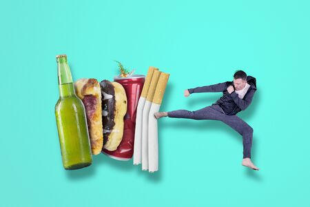 Caucasian man wearing sportswear while kicking cigarettes, beer and, fast food in the studio. Healthy lifestyle concept