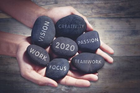 Closeup of unknown man holding pebbles of success future and number 2020 with wooden background