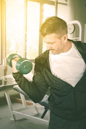 Portrait of Caucasian man lifting a dumbbell while exercising in the gym center at dusk time