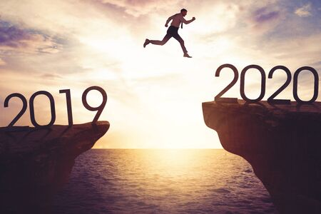 New year concept. Caucasian businessman jumping gap on the cliff from numbers 2019 to numbers 2020. Shot at sunrise time Reklamní fotografie