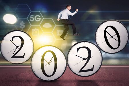 Caucasian businessman running above four clocks shaped number 2020 with 5G network symbol Reklamní fotografie