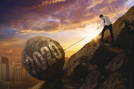 Young male entrepreneur pulling number 2020 in a stone with chains while walking on the cliff. Shot at sunrise time Reklamní fotografie