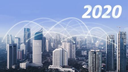 Aerial view of skyscrapers with numbers 2020 and network connection at morning time in Jakarta city