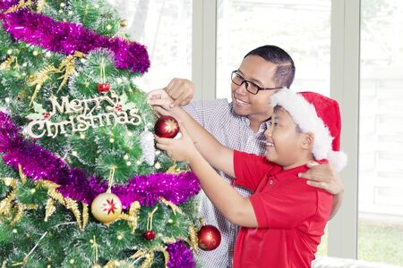 Preteen boy helped by his father to put an ornament on a Christmas tree at home