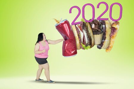 Picture of fat woman punching soft drink and fast food with number 2020 in the studio. Healthy lifestyle resolution concept