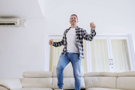 Low angle view of smiling man dancing and jumping on the couch in the living room. Shot at home Banco de Imagens