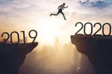 New year concept. Young businessman jumping gap on the cliff from number 2019 to number 2020. Shot at sunrise time