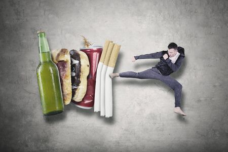 Caucasian man wearing sportswear while fighting with cigarettes, beer and, fast food. Healthy lifestyle concept