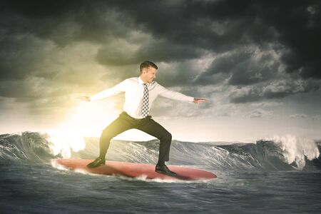 Caucasian businessman looks happy while surfing with surfboard on the waves of the ocean at sunset time