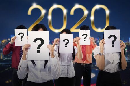Group of unknown business team covered their face by question marks with number 2020 background. Shot outdoors