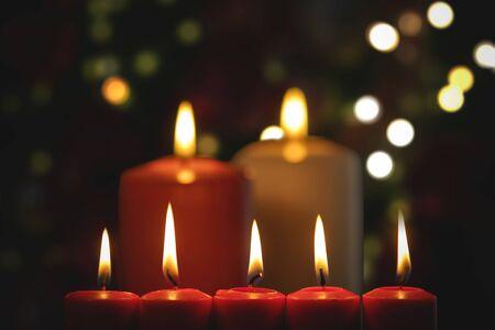Cinque candele rosse e due grandi candele con sfondo chiaro scintillante sfocato