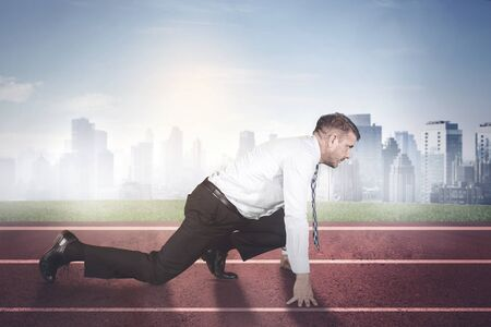 Side view of Caucasian businessman ready to run while kneeling on the track line with misty city background
