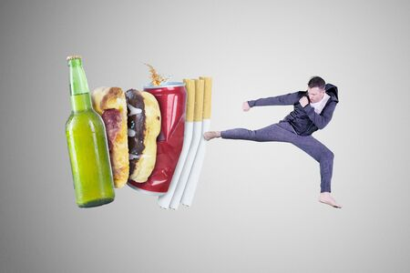 Young man wearing sportswear while kicking cigarettes, beer and, fast food in the studio. Healthy lifestyle concept