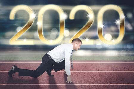 Side view of Caucasian businessman ready to run while kneeling on the track line with number 2020 background Фото со стока
