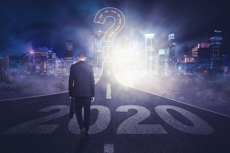 Back view of young businessman walking above numbers 2020 toward question mark on the road