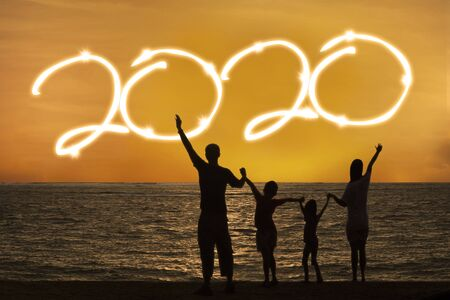 Silhouette of happy family standing on the beach while celebrating new year of 2020 at sunset time Reklamní fotografie