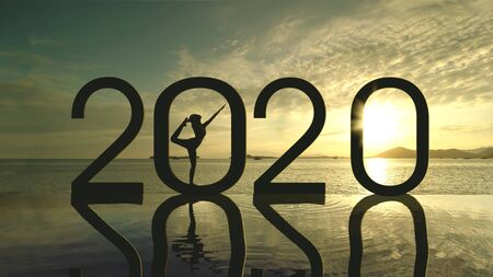Silhouette of an unknown woman practicing yoga with number 2020 on the beach at sunset time Stock Photo