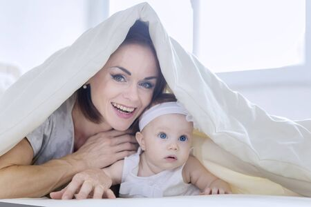 Cheerful mother plays with her baby girl while lying together under a blanket in the bedroom. Shot at home