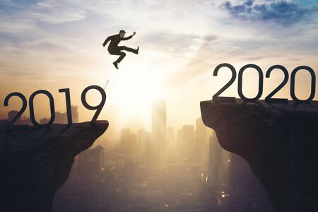 New year concept. Male manager jumping gap on the cliff from number 2019 to number 2020. Shot at sunrise time Reklamní fotografie