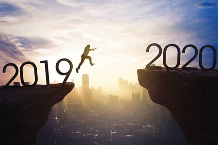 New year concept. Male entrepreneur jumping gap on the cliff from number 2019 to number 2020. Shot at sunrise time