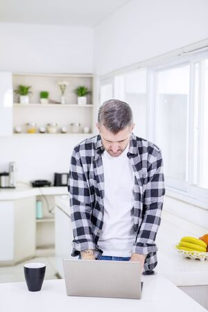 Portrait of mature man using a laptop while standing in the kitchen at morning time Reklamní fotografie