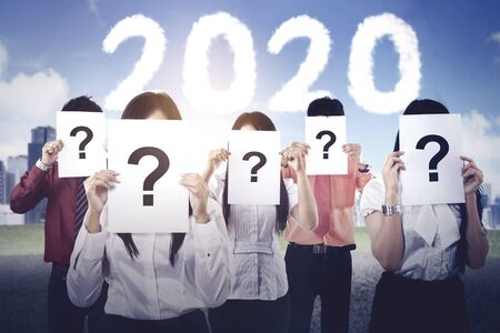 Group of unknown business people covered their face by question marks with number 2020 background. Shot outdoors Stockfoto