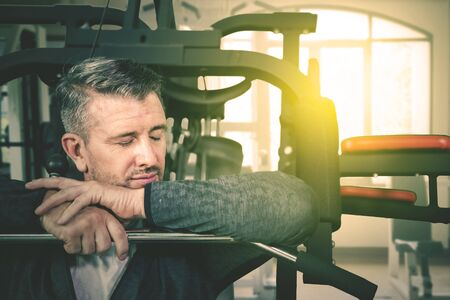 Close up of Caucasian man sleeping on the exercise machine while exercising in the gym center at dusk time
