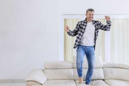 Picture of cheerful man dancing on the couch in the living room. Shot at home
