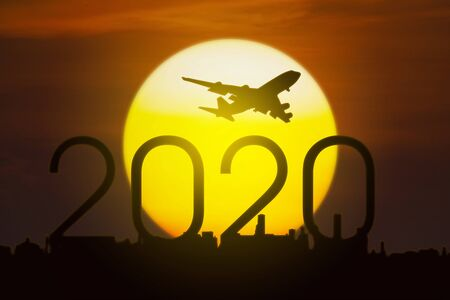 Silhouette of aircraft flying in the sky above numbers 2020 and city with a golden sun, shot at sunset time Reklamní fotografie