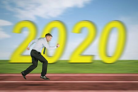 Side view of Caucasian businessman sprinting on the track line with blurred number 2020 background Фото со стока