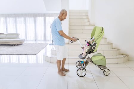 Side view of an old man playing with his grandchild in a stroller while standing in the living room at home