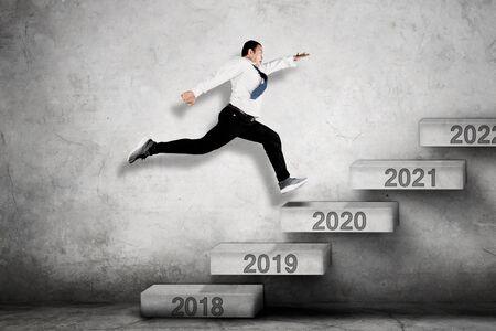 Bild eines männlichen Unternehmers, der auf der Treppe in Richtung Zahlen 2020 nach oben klettert
