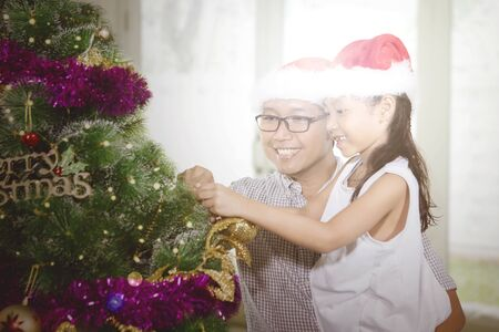 Cute little girl and her father putting ornaments on a Christmas tree at home with sunlight background 写真素材