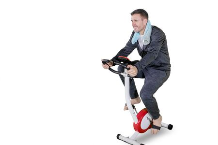 Caucasian man wearing sportswear while training with a spin bike in the studio, isolated on white background