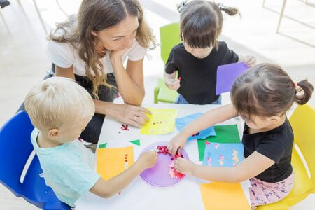 Top down view of female teacher and her students gluing trinkets on a paper in the kindergarten