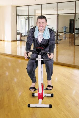 Portrait of Caucasian man exercising on a spin bike while wearing sportswear in the fitness center Фото со стока - 133668470