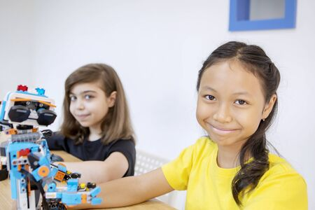 Two little students smiling at the camera while constructing a Lego robot together in the classroom