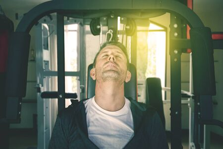 Young man falling asleep while resting on the exercise equipment after doing workout at fitness center. Shot at the gym