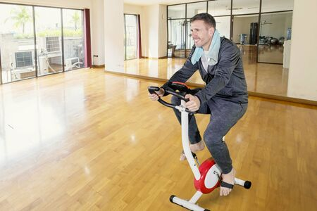 Caucasian man wearing sportswear while training with a spin bike in the fitness center Фото со стока - 133668660