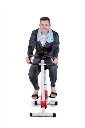Portrait of Caucasian man exercising on a spin bike while wearing sportswear in the studio Фото со стока - 133668775